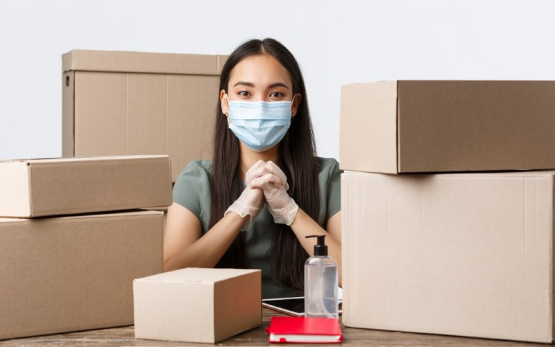 woman with medical mask sittingg among boxes