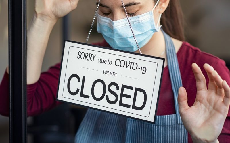 Shop owner with closed sign due to covid